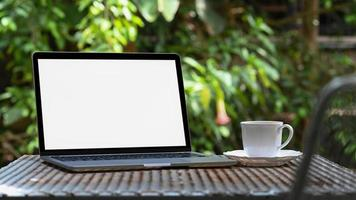 écran blanc d'ordinateur portable de maquette et tasse de café blanche sur la table de fer dans le jardin, fond d'arbre vert. photo