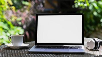 maquette d'écran vide pour ordinateur portable et tasse à café avec casque sur table en fer, fond d'arbre vert. photo