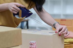 le vendeur emballe des cartons pour préparer l'expédition. photo