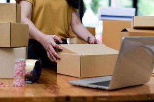 les vendeurs en ligne emballent des boîtes pour l'expédition, les achats en ligne, l'expédition de colis. photo