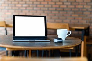 maquette d'ordinateur portable à écran blanc avec du café sur la table, prise de face. photo