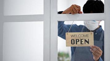 un jeune homme portant un masque tient une pancarte ouverte pour ouvrir le service. photo
