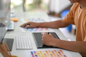 les graphistes professionnels travaillent sur des tableaux numériques avec des nuanciers sur leur bureau. photo