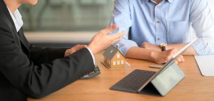 L'agent d'assurance recommande des forfaits d'assurance immobilière aux clients avec des tablettes et un modèle de maison. photo
