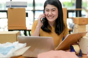 une femme vendant un produit en ligne parle au téléphone pour obtenir des informations et détient un fichier client. photo
