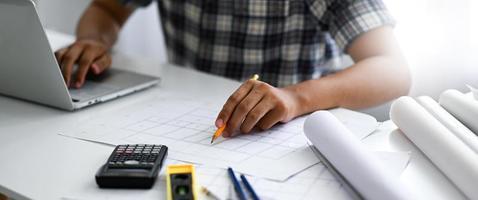l'architecte pointe un crayon sur un plan de maison et travaille sur un ordinateur portable. il vérifie et enregistre les résultats. photo