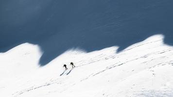 skieurs alpinistes à l'ombre des montagnes photo