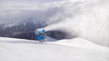 le canon tire de la neige dans la zone touristique des alpes suisses photo