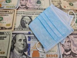 masque facial jetable sur le fond avec des billets d'un dollar américain photo