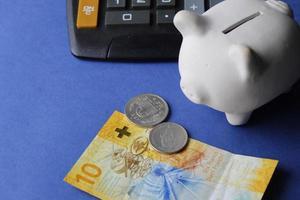 billet de banque suisse, pièces de monnaie, tirelire blanche et calculatrice sur le fond bleu photo