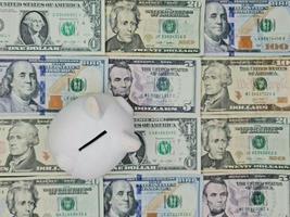 tirelire blanche et arrière-plan avec des billets d'un dollar américain, vue d'en haut photo