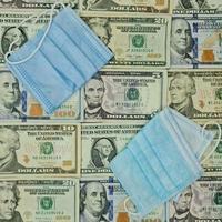 masques jetables et arrière-plan avec des billets d'un dollar américain, vue d'en haut photo