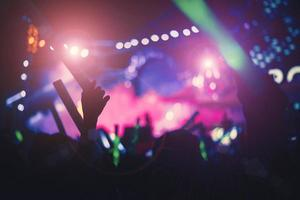 silhouettes de gens de la foule en concert des lumières de scène lumineuses photo