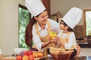famille asiatique heureuse dans la cuisine. mère et fils en toque préparant ensemble la nourriture dans la cuisine à domicile. mode de vie des gens et famille. concept de nourriture et d'ingrédients faits maison. deux thaïlandais en classe d'enseignement photo