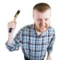 un homme en colère balance un gros marteau photo