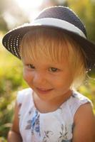 jolie petite fille souriante blonde dans un chapeau bleu photo