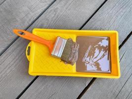 bac jaune de peinture verte avec pinceau sur fond de bois photo