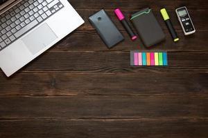 ordinateur portable, téléphone portable, marqueurs, disque dur supplémentaire, enregistreur vocal et autres éléments sur fond en bois. concept d'entreprise photo