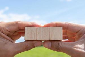 cube en bois vierge sur lequel vous pouvez mettre du texte ou une icône dans la main. photo