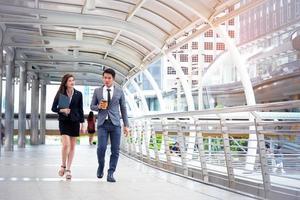 homme d'affaires et sa secrétaire marchant et parlant ensemble, concept d'entreprise, concept de relation, concept de travail d'équipe photo
