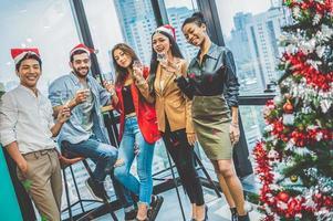groupe de travail d'équipe de collègues de diversité d'affaires célébrant la fête du nouvel an dans un contexte de bureau urbain moderne. amis ayant profité d'une fête avec un verre d'alcool ensemble. mode de vie multi éthique personnes photo
