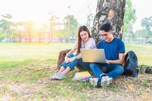 deux jeunes universitaires asiatiques discutant des devoirs et de l'examen final pour les tests avec un ordinateur portable. concept d'éducation et d'amitié. concept de bonheur et d'apprentissage. thème des amoureux et des amis photo
