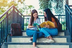 deux filles de beauté asiatiques lisant et donnant des cours particuliers pour l'examen final ensemble. étudiant souriant et assis sur l'escalier. concept d'éducation et de retour à l'école. thème des modes de vie et des portraits de personnes photo