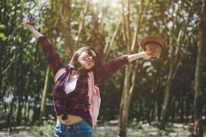 bonheur femme voyageuse asiatique dans la forêt avec les bras écartés et profiter de l'air frais. temps de détente et concept d'aventure. concept de vacances et de vacances. thème de fond bois et campagne photo