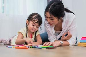 maman apprend à sa fille à dessiner en classe d'art. retour à l'école et concept d'éducation. thème enfants et enfants. thème home sweet home photo