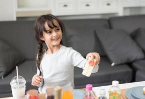 heureuse petite fille donnant un jouet de cuisine en sandwich en tant que chef dans le salon. ludique du concept d'éducation et de développement de l'enfant et du bonheur. apprentissage et loisirs de jolie fille. thème crèche et garderie photo