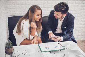 homme d'affaires et femme d'affaires analysant les tableaux de revenus et les graphiques dans un café. concept d'analyse et de stratégie d'entreprise. thème de bureau à l'intérieur photo
