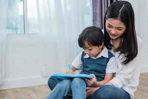 maman asiatique enseigne à un garçon mignon à dessiner ensemble au tableau. retour à l'école et concept d'éducation. thème de la famille et de la maison douce. thème des enfants d'âge préscolaire photo
