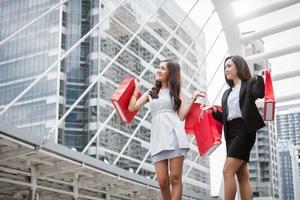 femmes d'affaires faisant leurs courses au centre commercial et sac de vente au détail en milieu urbain. riches filles heureuses acheteuses achetant un cadeau dans un magasin de produits lors de la vente du vendredi noir ou du cyber lundi. thème jeune consommatrice et cliente photo