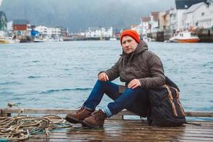 homme voyageur avec un sac à dos est assis sur la jetée de woode sur fond de maisons de pêche montagne et lac photo