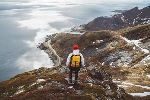 homme voyageur avec un sac à dos jaune debout sur des rochers sur fond de mer et de montagnes photo
