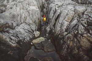 homme voyageur avec un sac à dos jaune portant un chapeau rouge debout sur le fond des rochers avec un bras levé. concept du gagnant. tirer de dos photo