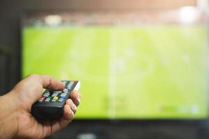 jeune homme tenant la télécommande de la télévision en regardant le programme de football. les mains pointant vers l'écran de télévision et l'allumant ou l'éteignant, sélectionnez la chaîne en regardant la télévision dans le salon, détendez-vous. photo