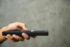 Jeune homme tenant la télécommande de la télévision photo