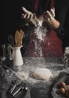 mains de boulanger répandant de la farine photo
