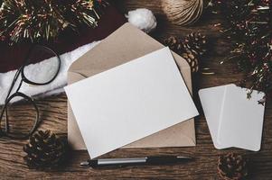 enveloppe, carte vierge, lunettes et un stylo sont placés sur du bois. photo
