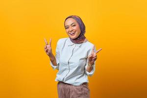 portrait d'une femme asiatique joyeuse montrant un signe de paix photo