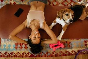 jeune femme noire riant en position couchée avec son chien sur un tapis photo