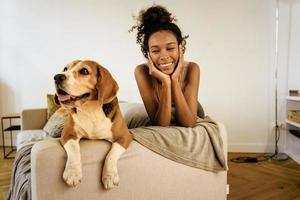 jeune femme noire riant tout en se reposant avec son chien sur le canapé photo