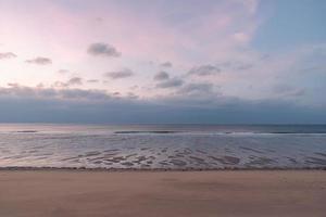 au petit matin au bord de la mer, le ciel et la plage sont légèrement rouges photo