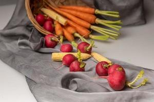 les radis rouges et oranges sont sur le drap blanc photo