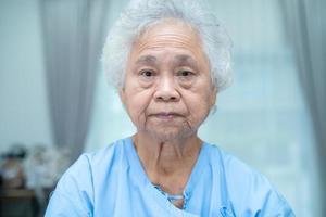 asiatique âgée ou âgée vieille dame patiente visage lumineux alors qu'elle était assise dans la salle d'hôpital de soins infirmiers, concept médical fort et sain photo