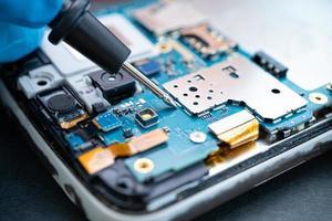 technicien réparant l'intérieur du téléphone portable en fer à souder. circuit intégré. le concept de données, de matériel, de technologie photo