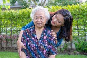femme âgée asiatique avec soignant marchant avec happy in nature park photo