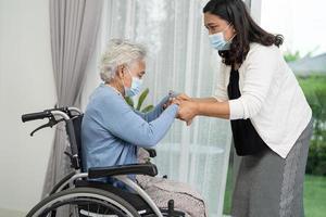aider une vieille dame asiatique âgée ou âgée assise sur un fauteuil roulant et portant un masque facial pour protéger la sécurité de l'infection covid-19 coronavirus photo