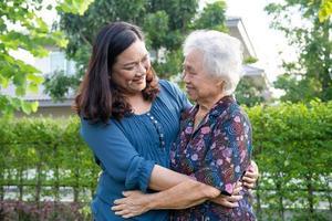 femme âgée asiatique avec aide soignante à pied avec amour et heureuse dans un parc naturel photo